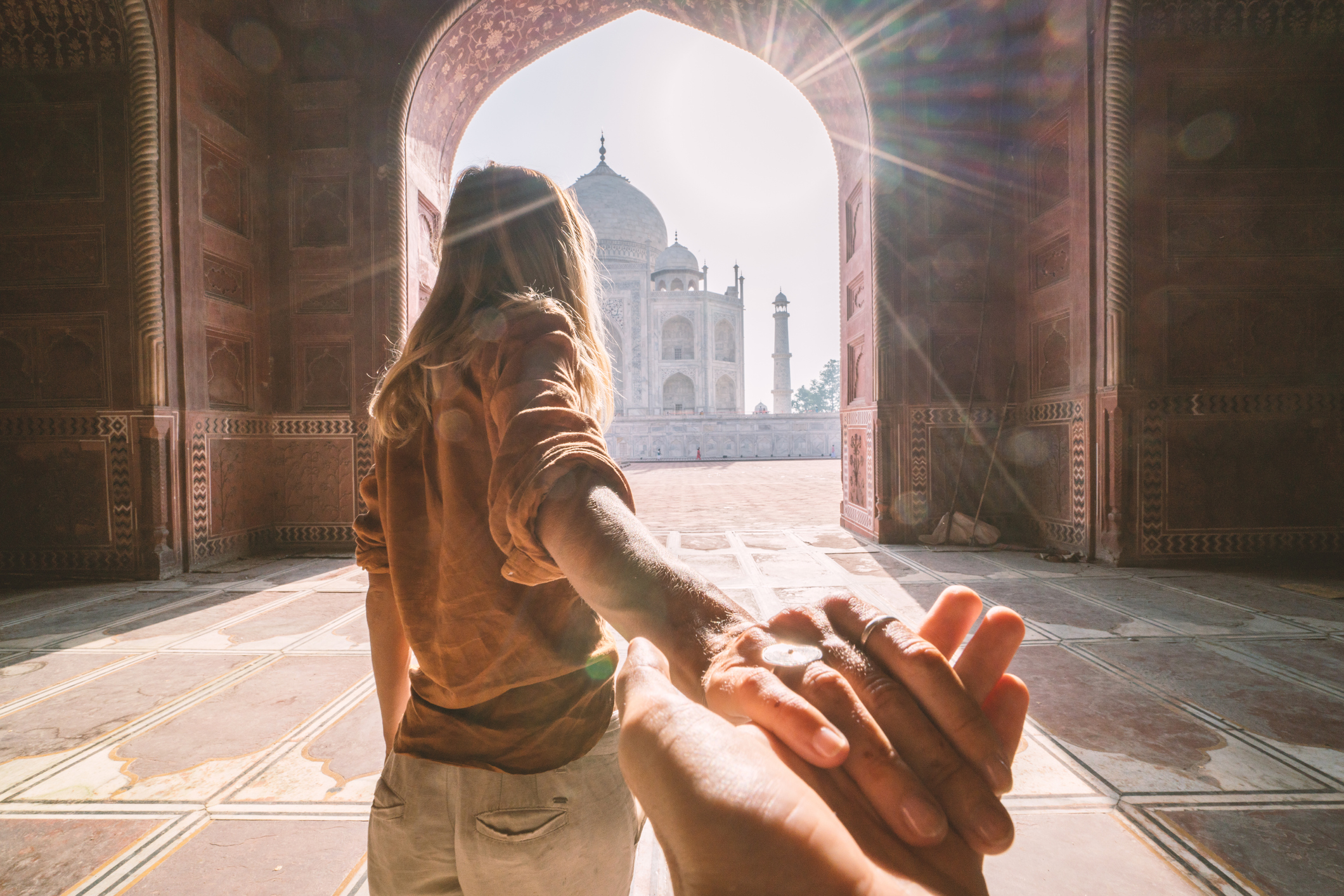 Woman holding man's hand in front of Taj Mahal
